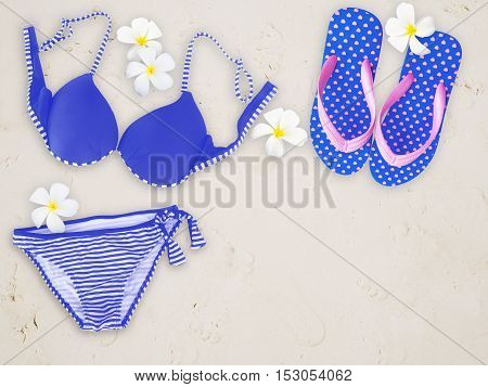 Fashionable woman swimming suit and flip flop on sand beach background.
