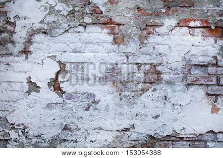 Chipped and peeling white paint on the surface of the old brick wall. Cracked crumbled grunge texture. Vintage background.