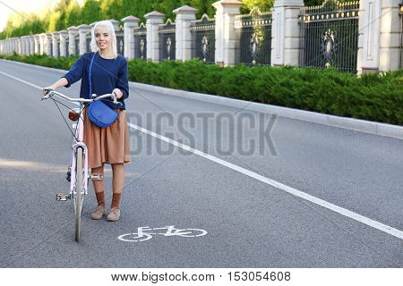 Pretty young woman with bicycle standing on road near bikeway sign