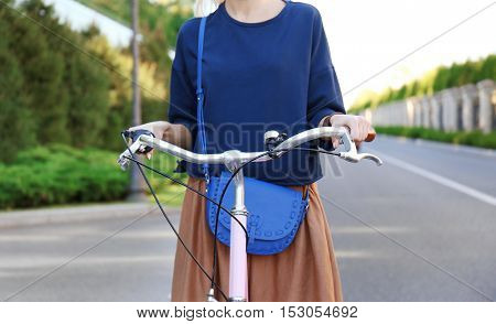 Young woman riding bicycle along road