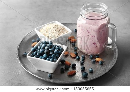 Mason jar with tasty smoothie and some ingredients on kitchen table