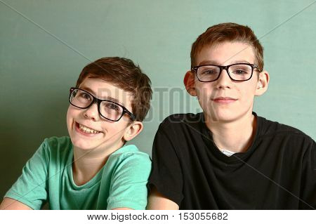 two teenager boys in myopia short sight glasses close up smile portrait