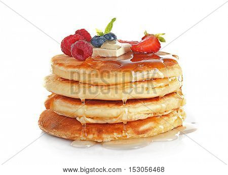 Stack of tasty pancakes with berries and syrup isolated on white