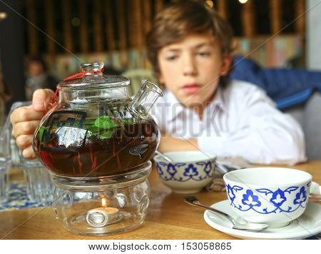 preteen boy with tea cattle keep hot on burning candle adn teacups close up portrait