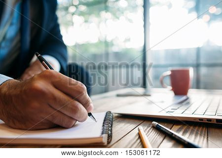 Male hand taking notes on the notepad. Handwriting. Creative writing. Inscription or recording of signs and symbols.