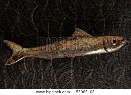 Handmade clay fish on wooden surface
