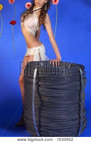 Attractive Girl Standing Near A Roll Of Wire