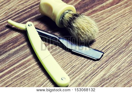 Men's cosmetics shaving brush and razor on a wooden background poster