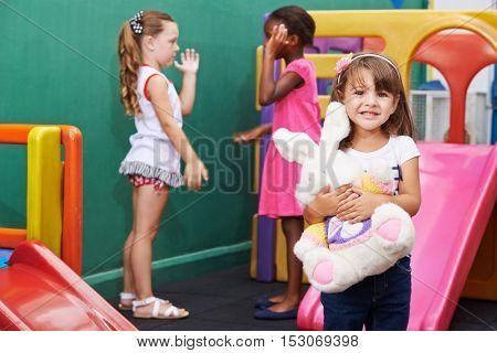 Happy girl standing with stuffed animal in a kindergarten