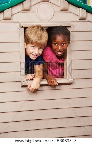 Two happy children looking together through a window in a playhouse