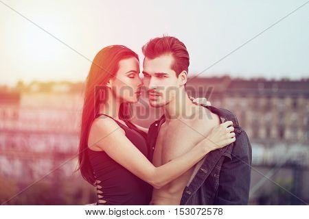 Sensual young couple posing outdoor brunette woman seduce man in sunset whispering