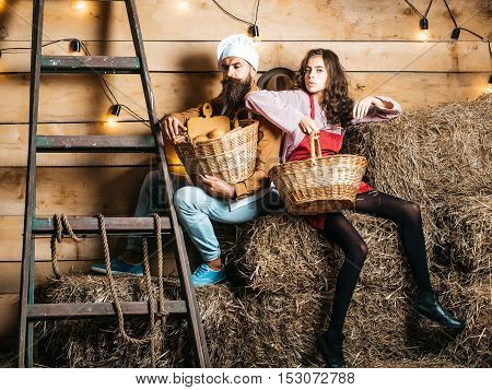 Handsome man chef cook or baker with beard and moustache in hat toque and cute girl cookee teenager in apron sit on straw bales with baskets on rustic background