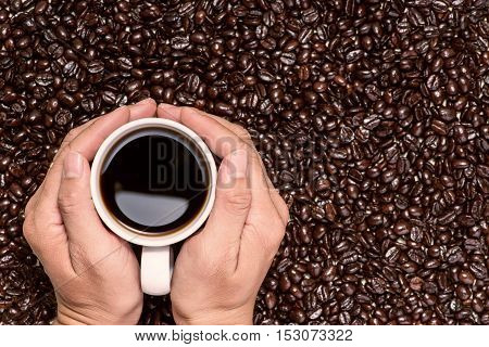 Hand holding a cup of black coffee and roasted coffee beans. View from above.