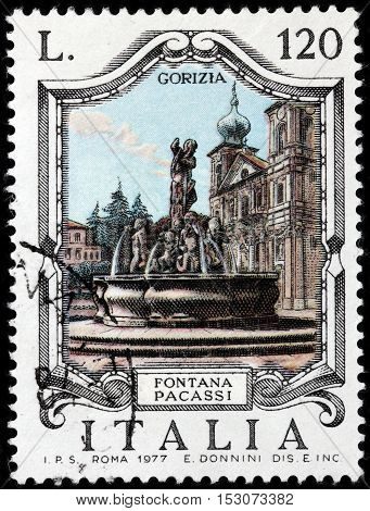 LUGA RUSSIA - JUNE 25 2016: A stamp printed by ITALY shows view of The Victory Square (Piazza della Vittoria) with famous Pacassi Fountain (Fontana Pacassi) in Gorizia Italy circa 1977