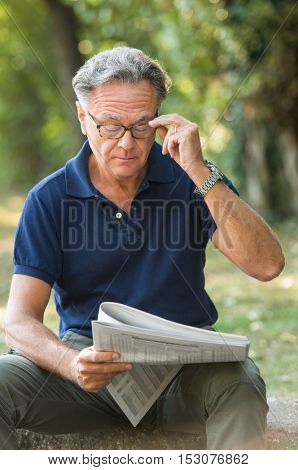 Mature man wearing eyeglasses while reading newspaper at park. Senior person adjusting glasses and reading news. Senior man relaxing at park and analyze stock market on newspaper.