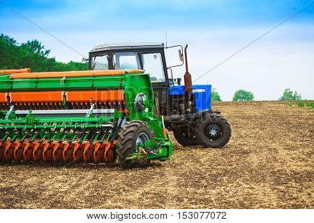 Tractor with a harrow to work the land field