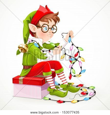 Cute boy elf sitting on a box with a gift and unravels a Christmas garland isolated on white background