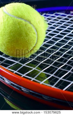 Closeup of  tennis racket with a tennis ball on black background.
