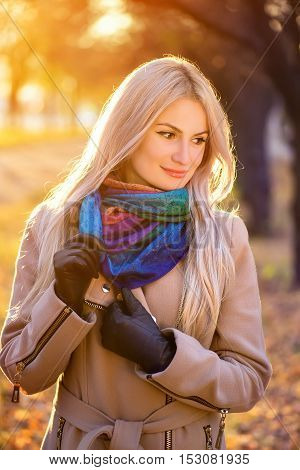 outdoors portrait of young blonde caucasian woman wearing autumn outfit outdoors in park on sunny fall day. Beautiful girl in beige coat and colorful scarf. Modern beautiful young woman in autumn park with sunshine