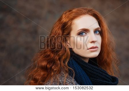 Close-up portrait of beautiful woman with red hair and blue eyes posing outdoors. Red-haired girl. Beautiful redhead woman with long curly hair against nature background looking at camera close-up fashion vogue outdoor