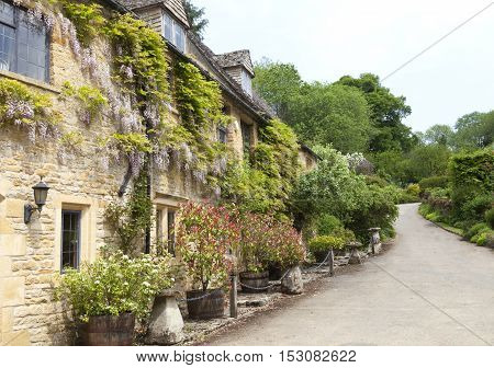 Old golden stone english houses with gardens in front of village path