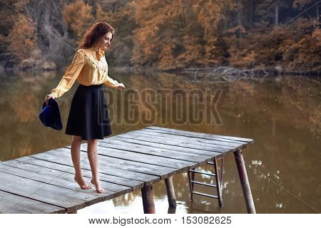 Dreaming girl with curly hair dancing barefoot on wooden bridge forest and river on background. Young woman on autumn background. Girl in vintage clothes
