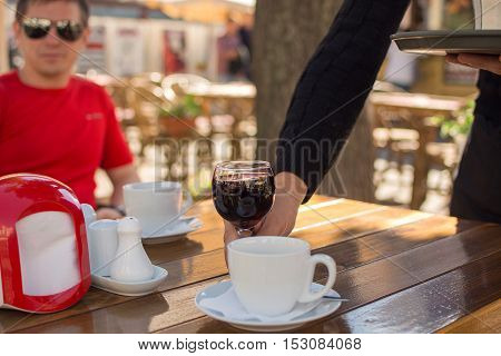 young man having lunch in the cafe on the table cup of coffee, a glass of wine, the waiter serves