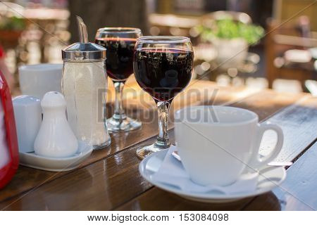 cup of coffee and two glasses of red wine on a table in a city café with a blurred background and bokeh