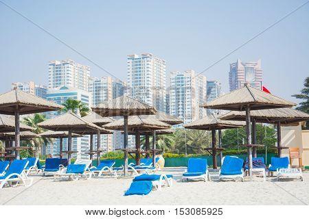 Dubai skyscrapers, palm, umbrella on the beach of the Persian Gulf