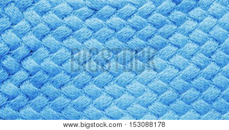 Blue cozy winter knitted background. Woolen fabric texture closeup. Textile texture blue background. Detailed warm yarn background. Knit cashmere wool. Natural woolen fabric, sweater fragment.