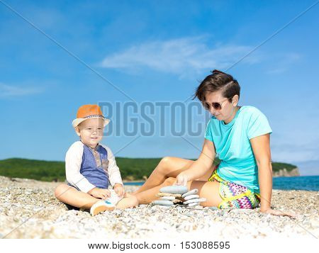 Mother and son making pebble stack near the sea