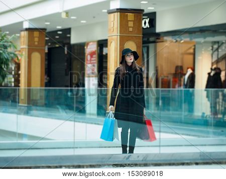 Beautiful elegant woman in a coat and hat with shopping bags. Shopping center