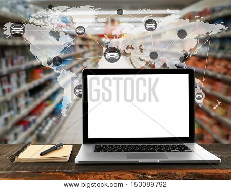 Laptop with blank screen on wooden table. Worldwide transport logistic network on supermarket interior background. Wholesale and retail concept.