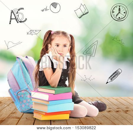 Cute little girl with stack of books sitting on wooden floor against blurred background. Diversity of school icons on background.