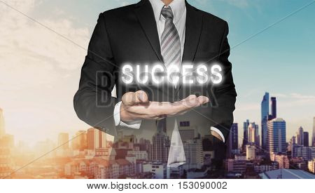 Businessman with bright SUCCESS text on hand, with defocus city view in sunrise, business success