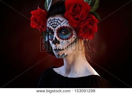 Scary woman wearing santa muerte makeup at halloween.