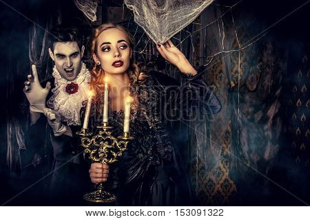 Bloodthirsty male vampire in medieval dress creeps up a young beautiful lady. Halloween.