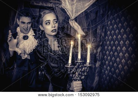 Bloodthirsty male vampire in medieval dress creeps up a young beautiful lady. Halloween. Black-and-white photo.