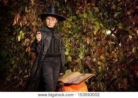 A boy in a costume of wizard with his magic wand conjures using magic book.  Halloween concept.