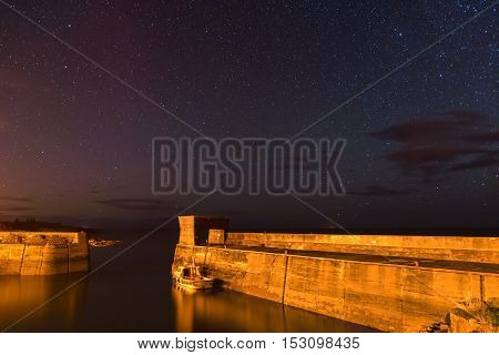 Craster Harbour at Night, with stars above on the Northumberland Coast, with just a hint of the Aurora Borealis