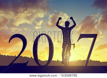 Cyclist on bicycle at sunset. Forward to the New Year 2017