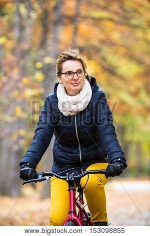 Urban biking - woman riding bike in city park