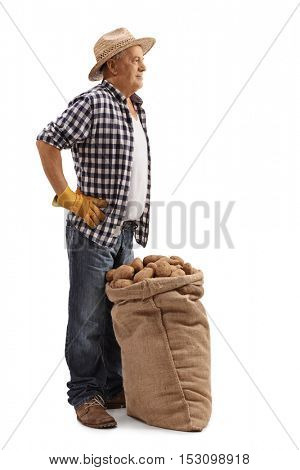 Full length profile shot of a mature farmer posing with a burlap sack full of potatoes isolated on white background