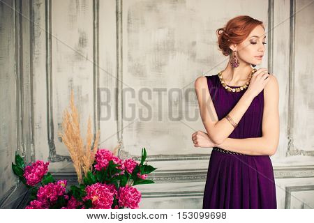 Woman in blue evening gown standing and looking to the left