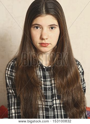 brown hair slavic teen gril with long hair in checked shirt close up portrait