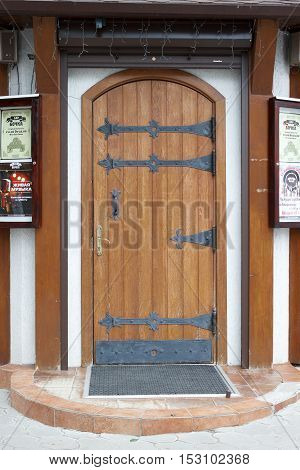 VOLGOGRAD RUSSIA - July 24 2016: The light wooden door is established on the street at an entrance to bar