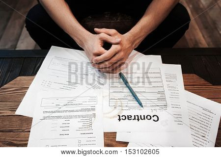 Top view on businessman sitting near lot of documents. Successful entrepreneur workplace. Business, routine, problems, bureaucracy, fortune, new contracts concept