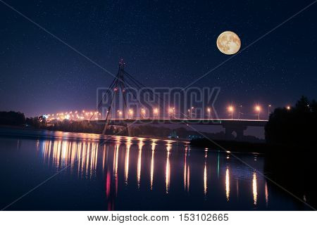 Moscow bridge in Kiev at night with colorful illumination and reflection in Dnieper river and big moon