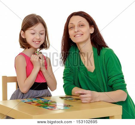 Joyful little girl and her mother at the table laid out cards with pictures.Isolated on white background.