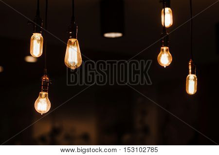 Edison lamps hanging from the ceiling. Vintage style light bulbs decorating room. Loft design background